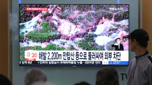 People watch a TV screen showing a satellite image of the Punggye-ri nuclear test site in North Korea during a news program at the Seoul Railway Station in Seoul, South Korea, Thursday, May 24, 2018. (AP Photo/Ahn Young-joon)