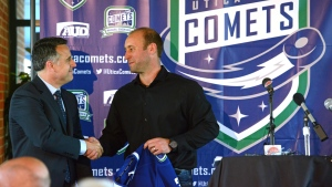 In this file photo, Laurence Gilman, left, the former Vancouver Canucks Vice President of Hockey Operations and Assistant General Manager, and Robert Esche, President of Mohawk Valley Garden, shake hands during a press conference on June 14, 2013. (Tina Russell/Observer-Dispatch via AP)