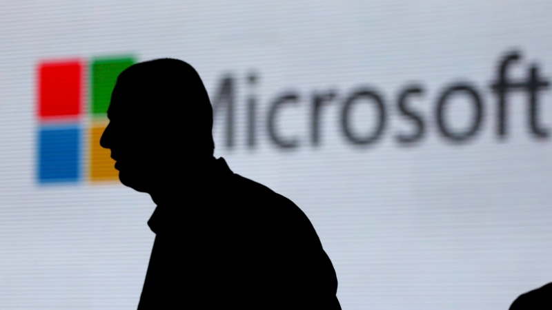 In this Nov. 7, 2017, file photo, an unidentified man is silhouetted as he walks in front of Microsoft logo at an event in New Delhi, India. (AP Photo/Altaf Qadri, File)