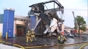 Firefighters work to extinguish a fire at the Suds and Jiffy Lube on Hespeler Road. (May 24, 2018)