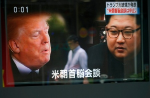 A man is reflected on a TV screen showing North Korean leader Kim Jong Un, right, and U.S. President Donald Trump in Tokyo Friday, May 25, 2018. (AP Photo/Eugene Hoshiko)