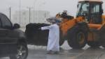 An Omani official gestures to a loader driver to tear away a road median to drain a flooded street in Salalah, Oman, Friday, May 25, 2018. (AP Photo/Kamran Jebreli)
