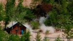 Smoke and debris go up in the air as the entrance to the north tunnel at North Korea's nuclear test site is blown up during a media tour of dismantling the test site at Punggye-ri, North Hamgyong Province, North Korea, Thursday, May 24, 2018. (APTN via AP)