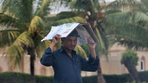A man covers his head under the rain in Salalah, Oman, Friday, May 25, 2018. (AP Photo/Kamran Jebreili)