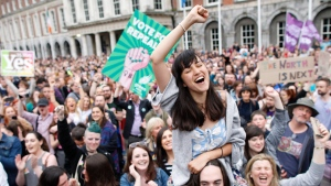 """A woman from the """"Yes"""" campaign reacts after the final result was announced in the Irish referendum on the 8th Amendment of the Irish Constitution at Dublin Castle, in Dublin, Ireland, Saturday, May 26, 2018. (AP Photo/Peter Morrison)"""