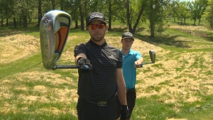 Visually impaired golfer Kiefer Jones (left) lines up a shot with the help of his friend Tobyn Larsen. (CTV Edmonton)
