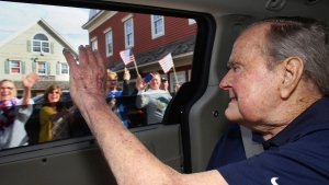 In this Sunday, May 20, 2018 photo provided by the office of former President George H.W. Bush, the former president waves to supporters as his motorcade arrives in Kennebunkport, Maine.