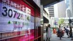 People walk past an electronic board showing Hong Kong share index outside a local bank in Hong Kong, Monday, May 28, 2018. (AP Photo/Vincent Yu)