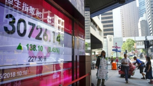 People walk past an electronic board showing Hong Kong share index outside a local bank in Hong Kong, Monday, May 28, 2018. (AP Photo/Vincent Yu)