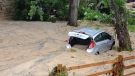 A car that was swept into the riverbank rests just off Main Street in flood-ravaged Ellicott City, Md., Monday, May 28, 2018. (AP Photo/David McFadden)