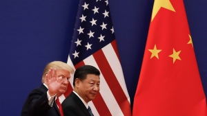 In this Nov. 9, 2017 file photo, U.S. President Donald Trump waves next to Chinese President Xi Jinping after attending a business event at the Great Hall of the People in Beijing. (AP Photo/Andy Wong, File)