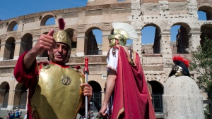 In this photo taken on April 8, 2018 people dressed as gladiators stand in front of the Colosseum in Rome, Italy. One can hardly see the treasures of Rome's top attractions these days without bumping arms with the hordes of tourists. (AP Photo/Virginia Mayo)