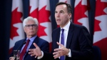 Finance Minister Bill Morneau and Natural Resources Minister James Carr speak at the National Press Theatre during a press conference in Ottawa on Tuesday, May 29, 2018. THE CANADIAN PRESS/Sean Kilpatrick