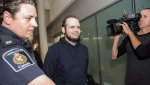 Joshua Boyle is escorted by authorities to a media availability at Toronto's Pearson International Airport on Friday, October 13, 2017. THE CANADIAN PRESS/Nathan Denette