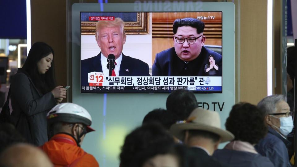 People watch a TV screen showing images of U.S. President Donald Trump, left, and North Korean leader Kim Jong Un during a news program at the Seoul Railway Station in Seoul, South Korea, Tuesday, May 29, 2018. (AP Photo/Ahn Young-joon)