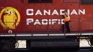 A Canadian Pacific Railway employee walks along the side of a locomotive in a marshalling yard in Calgary, Wednesday, May 16, 2012.
