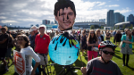 A protester holds a photo of Justin Trudeau and a globe covered in oil during a protest over the Trans Mountain pipeline expansion in Vancouver, B.C. in this 2018 file image. (THE CANADIAN PRESS/Darryl Dyck)