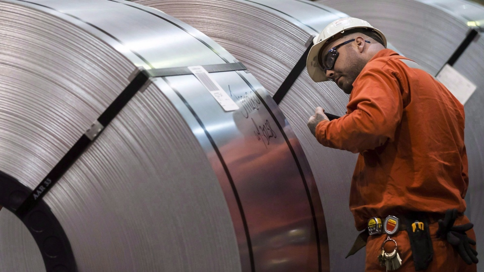 A Dofasco employee looks at rolls of coiled steel in Hamilton Ont., Tuesday, March 13, 2018. THE CANADIAN PRESS/Tara Walton