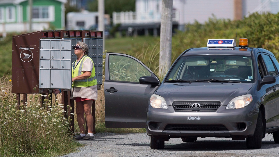 A Canada Post rural and suburban mail courier tends to a community mailbox in Eastern Passage, N.S. on Tuesday, Aug. 30, 2016. Talks between Canada Post and the Canadian Union of Postal Workers continue with the help of a mediator as they attempt to reach a negotiated agreement. Pay equity for rural letter carriers, who are mainly female, with their urban counterparts, and Canada Post's pension plan are among the issues on the table. (Andrew Vaughan/THE CANADIAN PRESS)