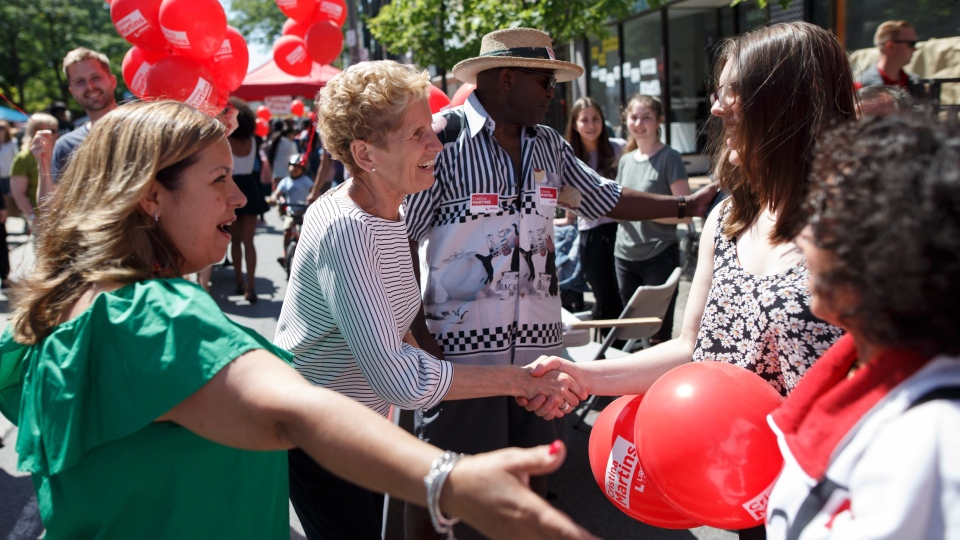 Ontario Liberal Party Leader Kathleen Wynne greets campaign volunteers during a campaign stop at a west end Toronto street festival on Saturday, June 2, 2018 in Toronto, Ontario. (THE CANADIAN PRESS/Cole Burston)