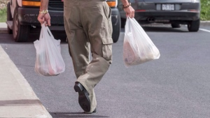 A shopper seen carrying bags in this file photo from 2016. The Kitchener Market announced that vendors would be offering pre-bagged goods where possible in order to limit the possible spread of COVID-19. THE CANADIAN PRESS/Paul Chiasson