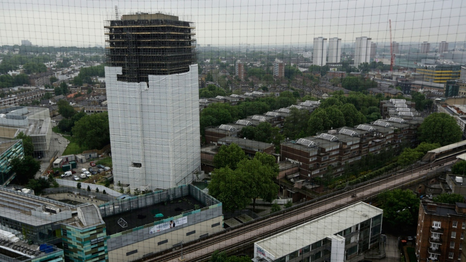Scaffolding covers the burnt out Grenfell Tower, almost one year on from the fire that killed 72 people, in London, Wednesday, May 30, 2018. (AP Photo/Matt Dunham)