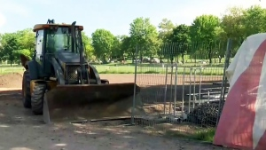 A bulldozer is parked on a softball field at Jeanne Mance field