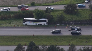 A bus sits on the side of highway 401 after crashing into a rock cut in Prescott, Ont., on Monday, June 4, 2018. (THE CANADIAN PRESS/Lars Hagberg)