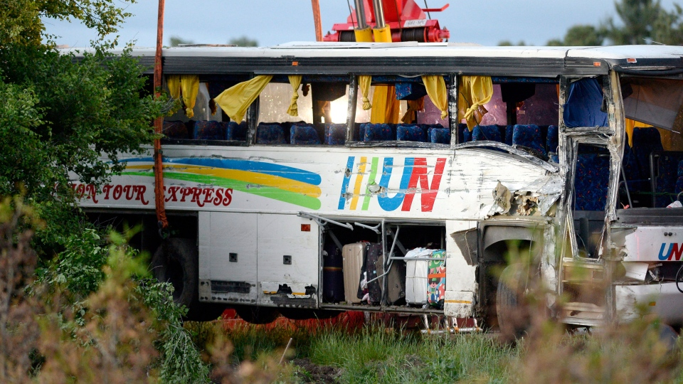 The damage to the side of a tour bus that was involved in a crash on Highway 401 West, near Prescott, Ont., is seen as tow operators work to remove it from a ditch on Monday, June 4, 2018. (THE CANADIAN PRESS/Justin Tang)