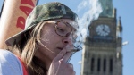 A woman smokes a joint during the annual 420 marijuana rally on Parliament hill on Wednesday, April 20, 2016 in Ottawa. The New Democrats are urging the Liberal government to decriminalize pot before they legalize it.Prime Minister Justin Trudeau campaigned on a promise to legalize, regulate and restrict access to marijuana, and his government plans to get started next spring THE CANADIAN PRESS/Justin Tang