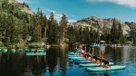 This July 24, 2017 photo provided by Wanderlust, participants work out on paddle boards during Wanderlust Squaw Valley 2017, in North Lake Tahoe, Calif. (Amanda Senior/Wanderlust via AP)