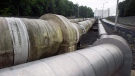 In this June 12, 2014, photo, pipes carrying liquified natural gas to and from a holding tank, seen in background, at Dominion Energy's Cove Point LNG Terminal in Lusby, Md. (AP Photo/Cliff Owen, File)