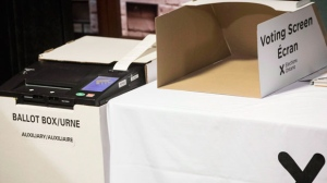 A vote tabulator (left) sits next to a voting screen as Ontario's Chief Electoral Officer Greg Essensa explains an electronic voting machine during a media availability in Toronto on Wednesday, May 9, 2018. (THE CANADIAN PRESS/Chris Young)