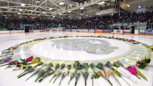 Flowers lie at centre ice as people gather for a vigil at the Elgar Petersen Arena, home of the Humboldt Broncos, to honour the victims of a fatal bus accident in Humboldt, Sask. on Sunday, April 8, 2018. (THE CANADIAN PRESS/Jonathan Hayward)