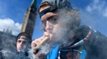 A man smokes a marijuana joint during the annual 4/20 celebration on Parliament Hill in Ottawa on Friday, April 20, 2018. (THE CANADIAN PRESS/Justin Tang)