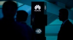 FILE - In this June 26, 2016 file photo, visitors attend a launch event for the Huawei MateBook in Beijing. (AP Photo/Mark Schiefelbein)