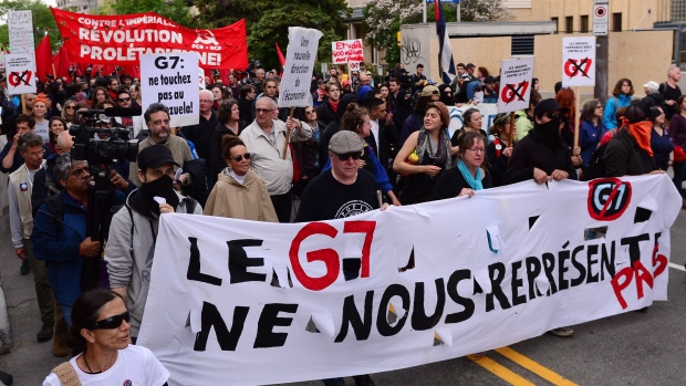 Protesters carry a large banner at a G7 protest in Quebec City on Thursday, June 7, 2018. THE CANADIAN PRESS/Paul Chiasson