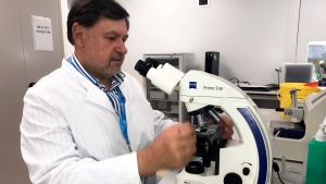 In this photo taken on Wednesday, June 6, 2018 picture, Alexandru Rafila, who heads a laboratory at the Matei Bals National Institute for Infectious Diseases, operates a microscope in Bucharest, Romania. (AP Photo/Olimpiu Gheorghiu)