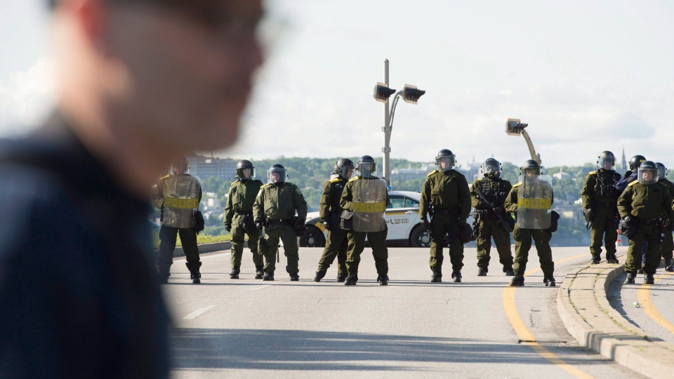 Police officers in riot gear protect highway 440, Friday, June 8, 2018 in Quebec City. (THE CANADIAN PRESS/Jacques Boissinot)