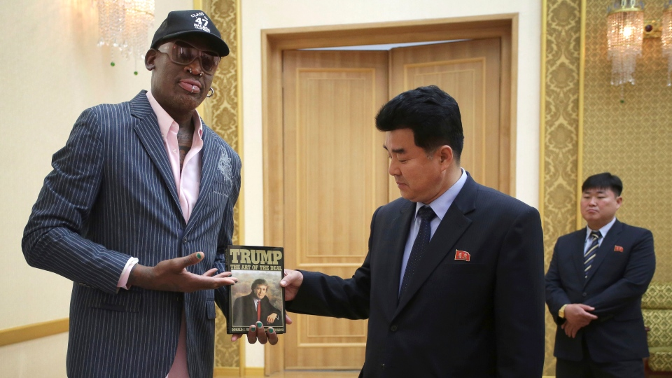 "In this June 15, 2017, file photo, former NBA basketball star Dennis Rodman presents a book titled ""Trump The Art of the Deal"" to North Korea's Sports Minister Kim Il Guk in Pyongyang, North Korea. (AP Photo/Kim Kwang Hyon, File)"