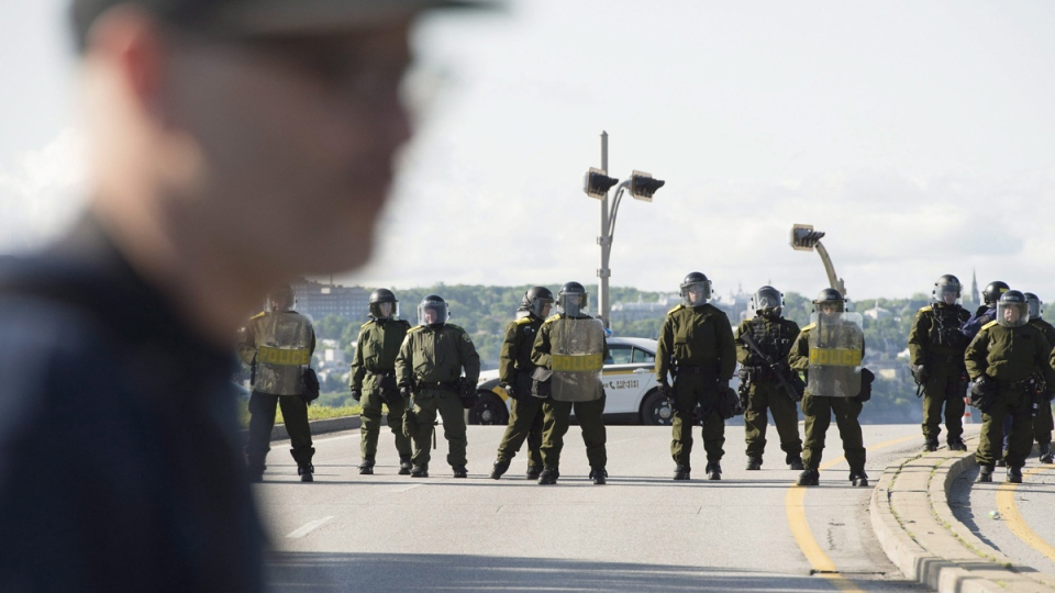 Police officers in riot gear on Highway 440 in Quebec City, on June 8, 2018. (Jacques Boissinot / THE CANADIAN PRESS)