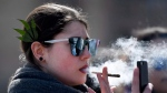 A woman smokes a joint during the annual 4/20 marijuana celebration on Parliament Hill in Ottawa on Friday, April 20, 2018. (THE CANADIAN PRESS/Justin Tang)