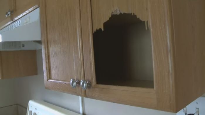 Damage to a cupboard in a rental home is shown on June 7, 2018
