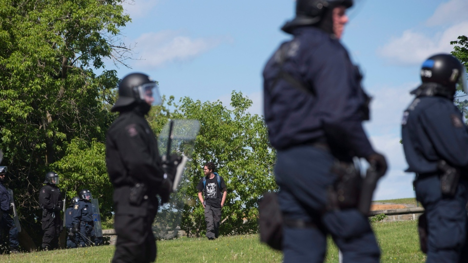 A protester tries to evade a police cordon up a demonstration during the G7 Summit in Quebec City on Friday, June 8, 2018. THE CANADIAN PRESS/Chris Young