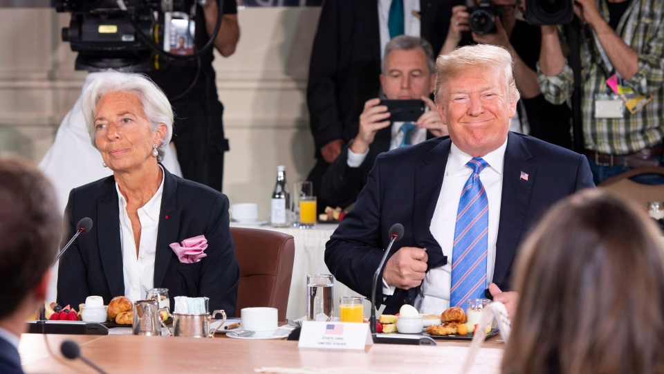 U.S. President Donald Trump, right, takes his seat after arriving late for the G7 and Gender Equality Advisory Council Breakfast, as IMF Managing Director Christine Lagarde looks on, left, at the G7 leaders summit in La Malbaie, Que., on Saturday, June 9, 2018. THE CANADIAN PRESS/Justin Tang