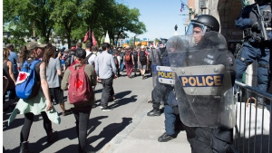 Police in riot gear watch as protesters march through in Quebec City on Saturday June 9, 2018, as the G7 summit closes. THE CANADIAN PRESS/Jacques Boissinot