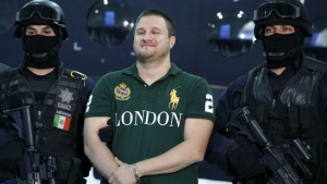 Texas-born fugitive Edgar Valdez Villarreal, also known as 'La Barbie,' centre, reacts during his presentation to the media after his arrest in Mexico City on Aug. 31, 2010. (AP Photo/Alexandre Meneghini)