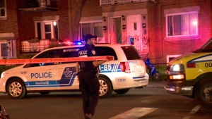 A Montreal police officer unrolls crime scene tape at Centrale St. and 9th Ave. in LaSalle (CTV Montreal/Cosmo Santamaria)