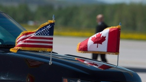 Canadian and United States flags are seen on a vehicle in the motorcade as U.S. President Donald Trump arrived at the airport at CFB Bagotville, Que. for the annual summit of G7 leaders on Friday, June 8, 2018 (THE CANADIAN PRESS/Andrew Vaughan)