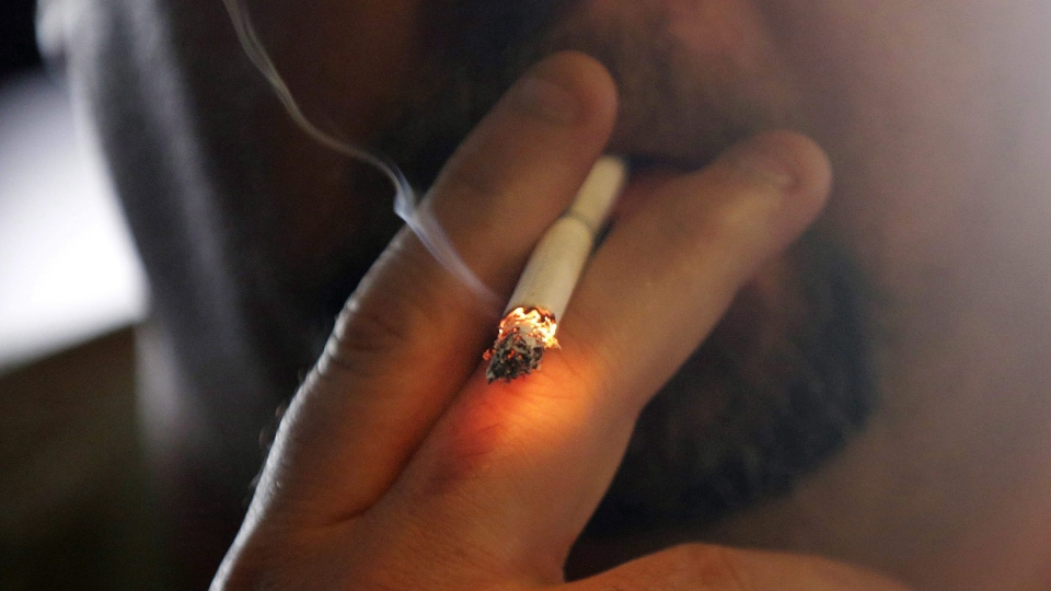 In this April 21, 2015 file photo, a man smokes a cigarette in New Orleans. (AP Photo/Gerald Herbert)